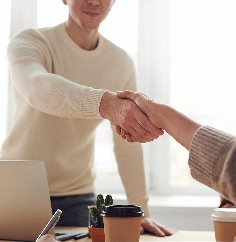 Nuori mies kättelee naista toimistossa