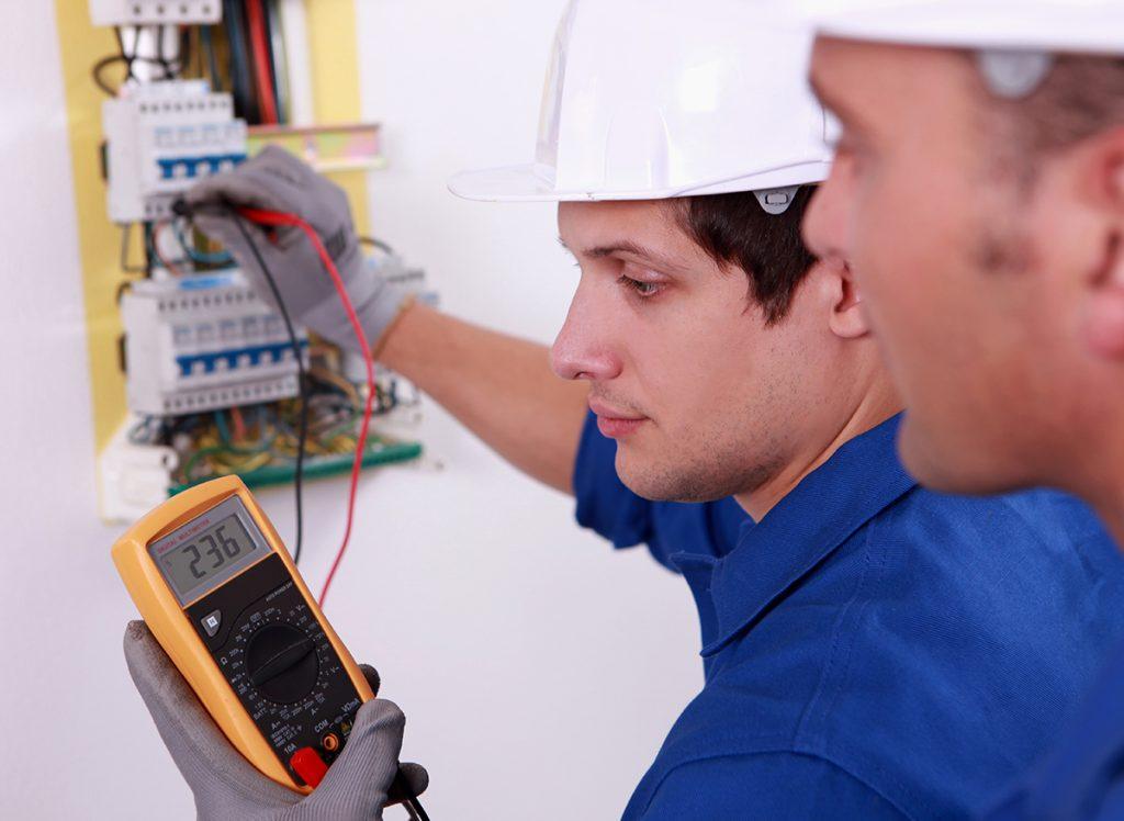 mies mittaa sähkömittarilla kaapista