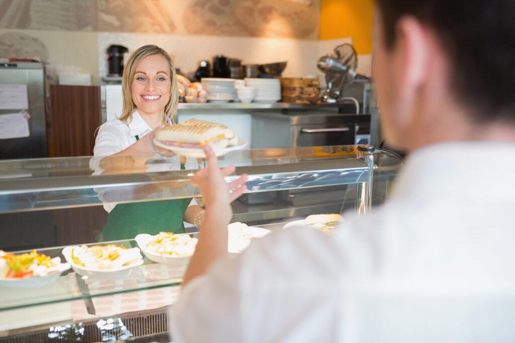 nainen ojentaa leipää asiakkaalle