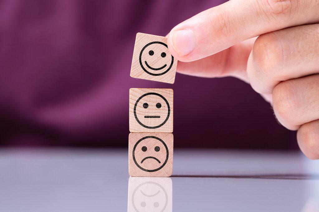Ihminen asettaa kolme hymiöpalikkaa päällekkäin, alimpana surullinen, keskellä neutraali ja ylempänä hymyilevä hymiöpalikka.